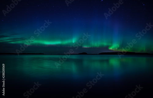 Keuken foto achterwand Noorderlicht Northern lights dancing over calm lake in Farnebofjarden national park in Sweden.