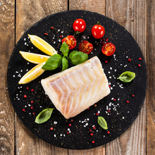 Fresh Raw Cod With Herbs Served On Black Stone On Wooden Table