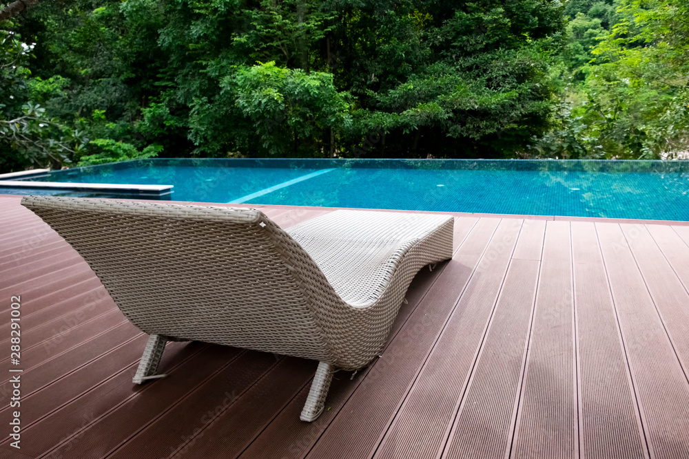 Fototapeta Poolside deckchairs or sun bed on terrace with blue swimming pool private view with forest background. Relaxing in vacation holiday concept.