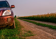 A red crossover stands on the side of a dirt road. Country road along the golden rye field.