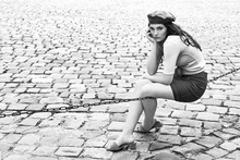 Young Beautiful Brunette Emotional Girl Dressed In Retro Vintage Style In The Old European City Sits Of A Chain
