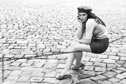 young-beautiful-brunette-emotional-girl-dressed-in-retro-vintage-style-in-the-old-european-city-sits-of-a-chain