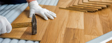 The Builder, Man Is Engaged In Laying Laminate Wood Floor In The Room - Repair And Finishing Work