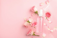 Flat Lay Composition With Rose Essential Oil And Flowers On Pink Background, Space For Text