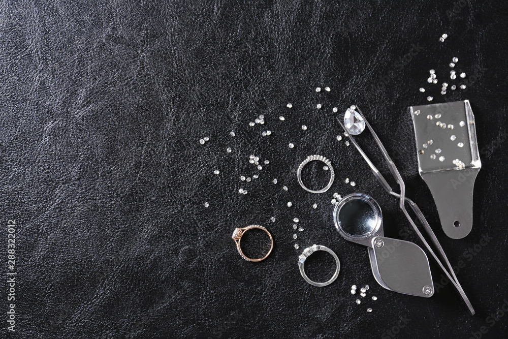Fototapeta Flat lay composition with precious stones and jewelry tools on black leather background, space for text