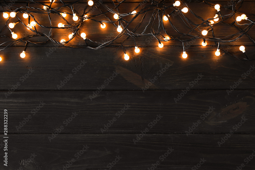 Leinwandbild Motiv - New Africa : Glowing Christmas lights on dark wooden background, top view. Space for text