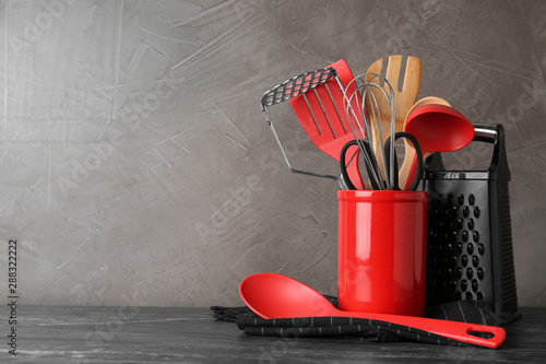 Fotomural  Holder with kitchen utensils on grey table against grey stone background