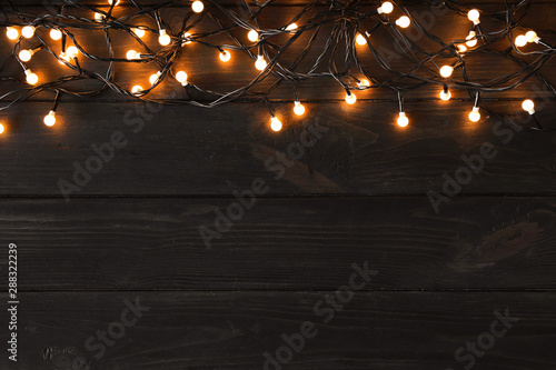 Foto auf AluDibond Logo Glowing Christmas lights on dark wooden background, top view. Space for text