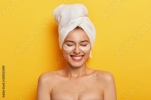 Cuadros en Lienzo  Headshot of satisfied beautiful naked woman applies white patches under eyes to