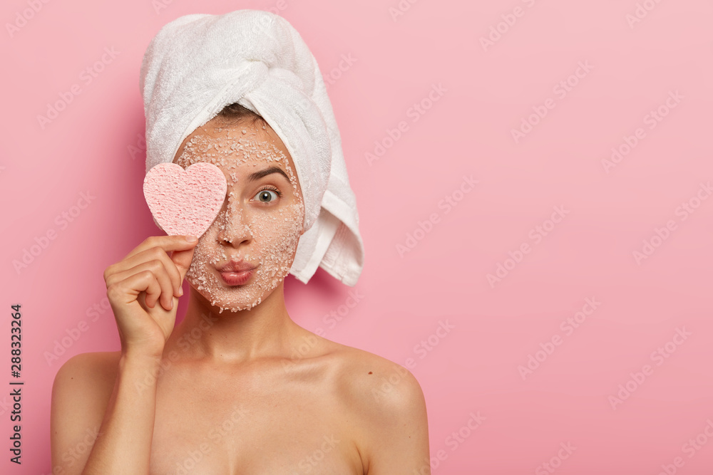 Fototapety, obrazy: Reducing pores and cleansing concept. Attractive female applies sea salt mask on face, has luxurious feelings from beauty treatments, covers eye with heart shaped sponge, pampers complexion.