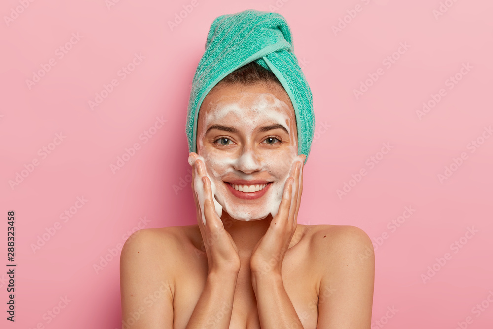 Fototapeta Positive young female has toothy smile, has perfect teeth, pats skin with liquid sanitary soap, washes with foaming gel, wakes up in morning for having beauty routine, isolated on pink background