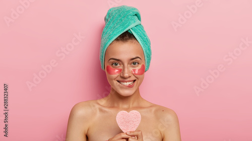 Headshot of beautiful young female bites lips with pleasure, enjoys spa treatment, applies cosmetic collagen patches under eyes, has perfect smooth skin isolated on pink background Wallpaper Mural