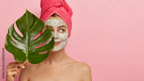 Fototapeta Horizontal shot of pretty thoughtful European woman holds big green leaf, looks pensively aside, stands naked, applies clay mask on face, models against pink background
