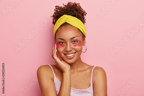 Portrait of smiling Afro American woman with under eye patches, relieves puffine Fototapet