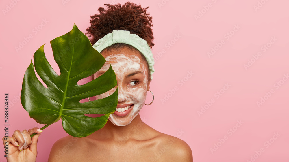 Fototapeta Pleased dark skinned woman stands naked alone, looks aside with cheerful expression, holds green leaf near face, expresses good emotions, enjoys softness from washing face, wears headband, earrings
