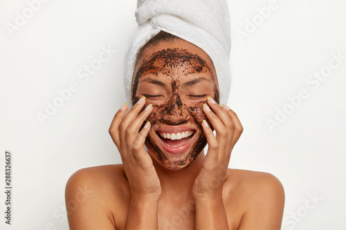 Fototapeta Portrait of cheerful smiling dark skinned woman applies natural coffee mask, makes circular motions with hands and massages skin, stimulates facial blood supply, wears wrapped towel on head