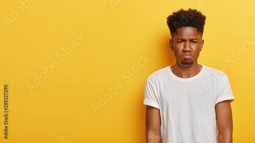 Obraz Photo of dejected displeased dark skinned man dislikes something, being in low spirit after failure, has little beard and Afro hairstyle, dressed casually, models over yellow wall. Negative emotions - fototapety do salonu