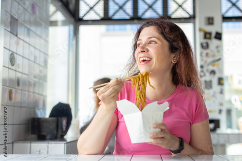 Valokuva  Close-up portrait of young pretty girl eating chinese noodles with wooden chopsticks sitting in a cafe