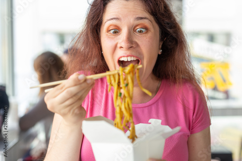 Valokuvatapetti Close-up portrait of an amusing crazy young pretty girl eating chinese noodles with wooden chopsticks sitting in a cafe