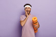 canvas print picture - Positive Caucasian man stands with rolled up karemat, touches cheek, wears headband and t shirt, stands against purple background has fitness workout regularly, waits for coach, motivated for training
