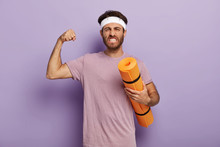 Motivated Powerful Man Stands With Fitness Mat, Enjoys Yoga As Sport And Hobby, Raises Arm And Shows Muscle, Clenches Teeth, Wears Headband, Violet T Shirt. Balance Your Life, Lead Healthy Lifestyle