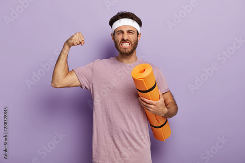 Fotomural Motivated powerful man stands with fitness mat, enjoys yoga as sport and hobby, raises arm and shows muscle, clenches teeth, wears headband, violet t shirt