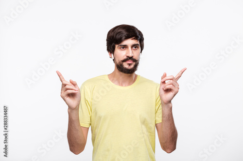 Fotografie, Obraz  Pretty brunet bearded man in a yellow t-shirt  with moustaches enjoying music listening songs with wireless ear buds isolated over white background