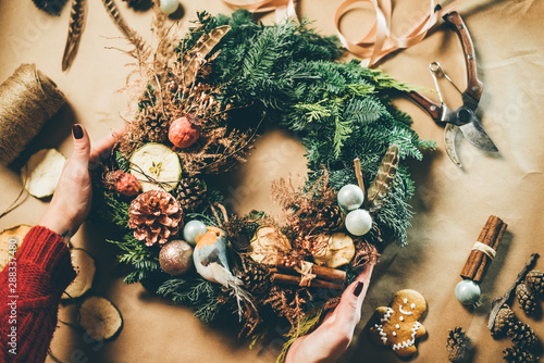 Fototapeta Top view Christmas wreath on craft background, pretty famales hands decorate christmas wreath. obraz