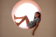 Young Barefoot Girl Resting In A Circular Opening