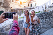 Two female friends photographed by friend on smartphone