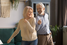 Active Senior Couple Have Fun Dancing In Living Room