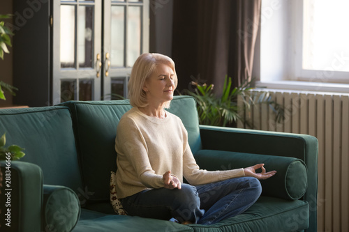 Stampa su Tela  Calm senior woman meditating on couch at home