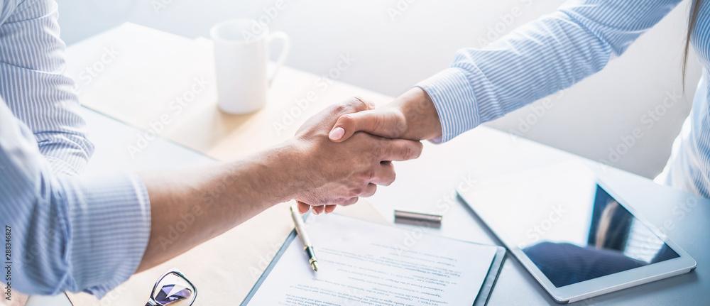Fototapeta Business people shaking hands, finishing up meeting.