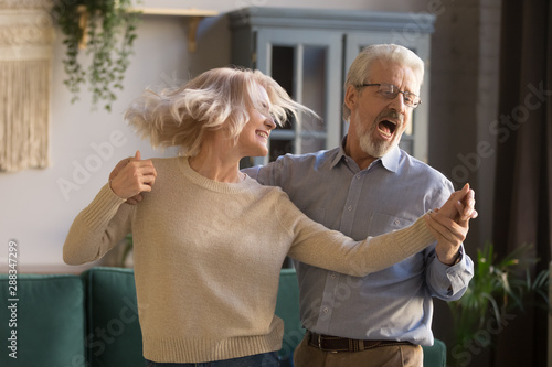 Active happy mature couple have fun dancing at home