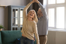 Overjoyed Senior Couple Relax Dancing At Home
