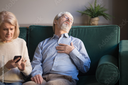 Anxious wife call emergency for husband having heart attack Canvas Print