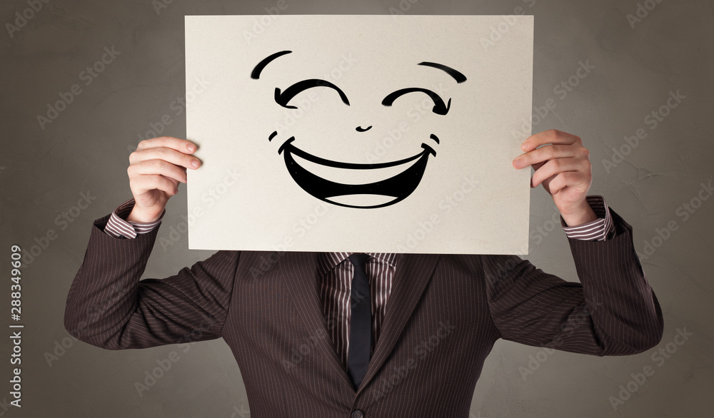 Fototapeta Casual person holding a paper in front of his face with drawn emoticon face