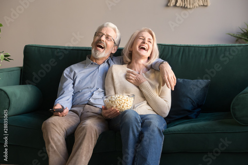 Fotografia  Excited mature couple laughing while watching comedy movie.