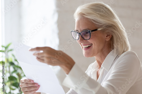 Photo Stands Coffee bar Happy senior woman read good news in paperwork document
