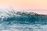 Bliska fal oceanicznych budujących się przed rozbiciem na brzeg plaży w pobliżu autostrady Pacific Coast. Podczas zachodu słońca tło ma wysoki kolor różowy, fioletowy i czerwony, aby uzyskać dramatyczny zachód słońca. - 288367642