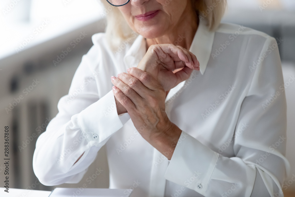 Fototapety, obrazy: Senior woman worker suffering from wrist spasm or strain