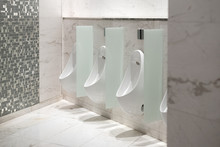 White Ceramic Urinals With The Automatic Flush System In The Public Toilet In A Shopping Mall.