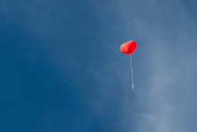 Red Heart Shaped Balloon In Front Of Blue Sky With Clouds
