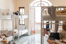 Hostel's Dormitory With Bunk Beds And Sleeping Travelers. Real Hostel's Interior With Some Mess.
