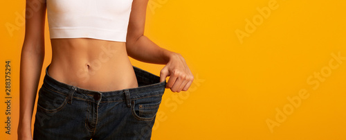 Obraz Unrecognizable Girl In Oversize Jeans Posing On Yellow Background, Cropped - fototapety do salonu