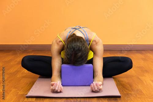 Carta da parati  Woman in butterfly yin yoga asana with forehead resting on purple prop
