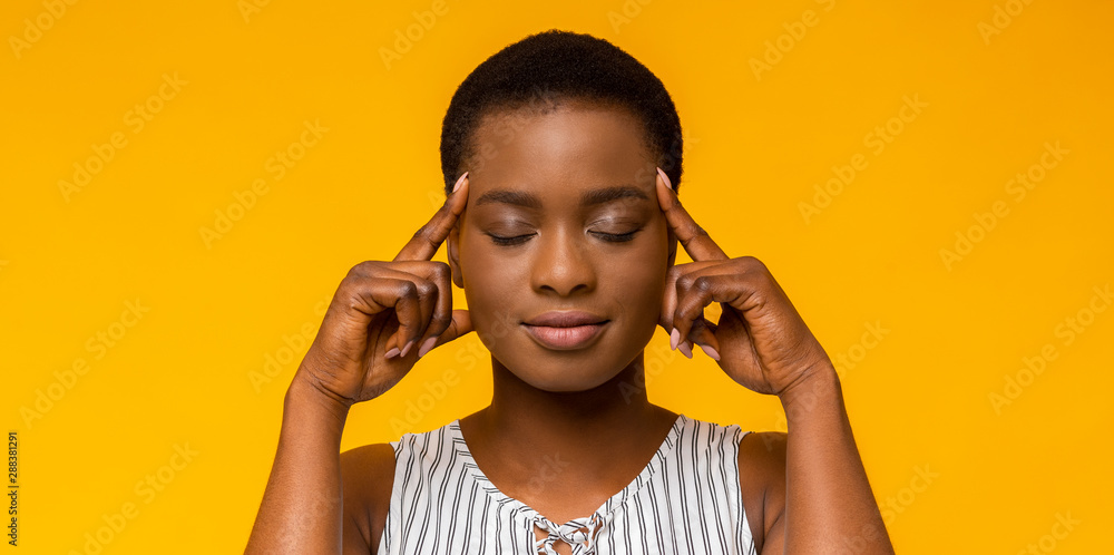 Fototapeta African american woman thinking hard with eyes closed