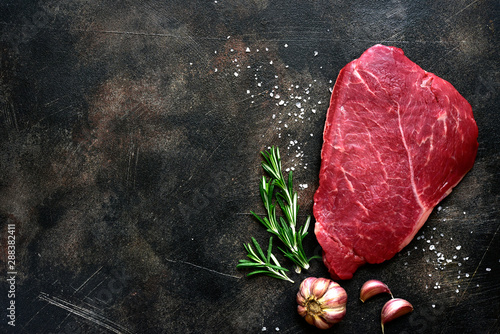 Raw beef steak with spices. Top view with copy space.