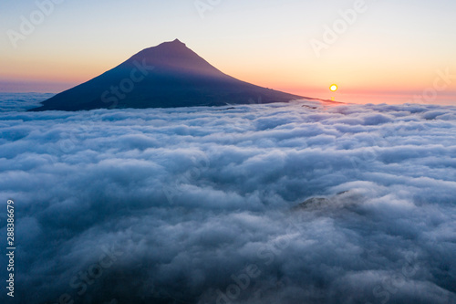 Photo sur Toile Bleu nuit Aerial image with magical sunset over a low cloud layer covering Pico Island, with Ponta do Pico (Mount Pico)