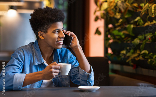 Fotografie, Obraz  Young afro man talking on mobile phone and smiling